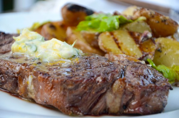 Grilled Strip Steak with Thyme Orange Shallot Compound Butter and Grilled Potatoes with Crumbled Bacon Vinaigrette.